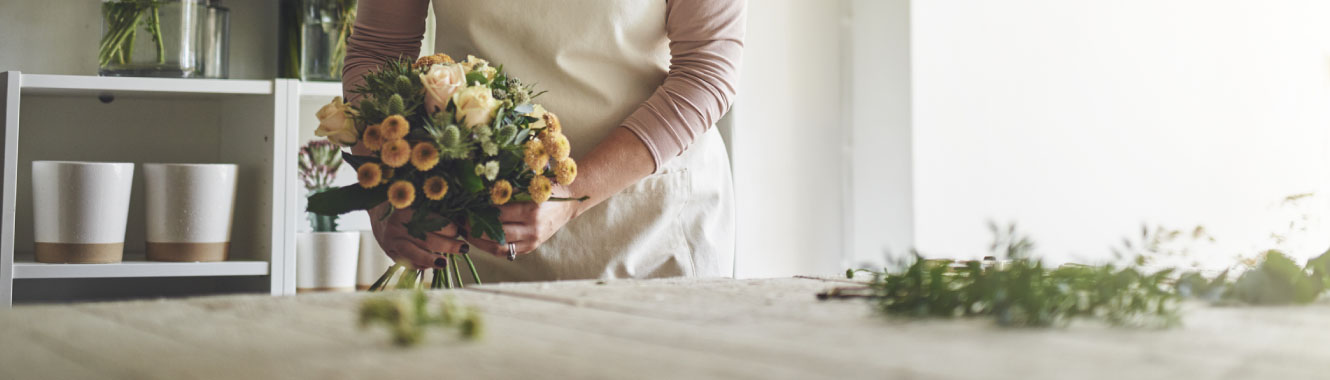 A woman's hands are tieing a bouquet of flowers together.