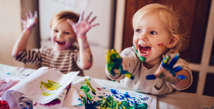 Two toddlers playing with finger paint and smiling. They have paint all over their hands and faces.