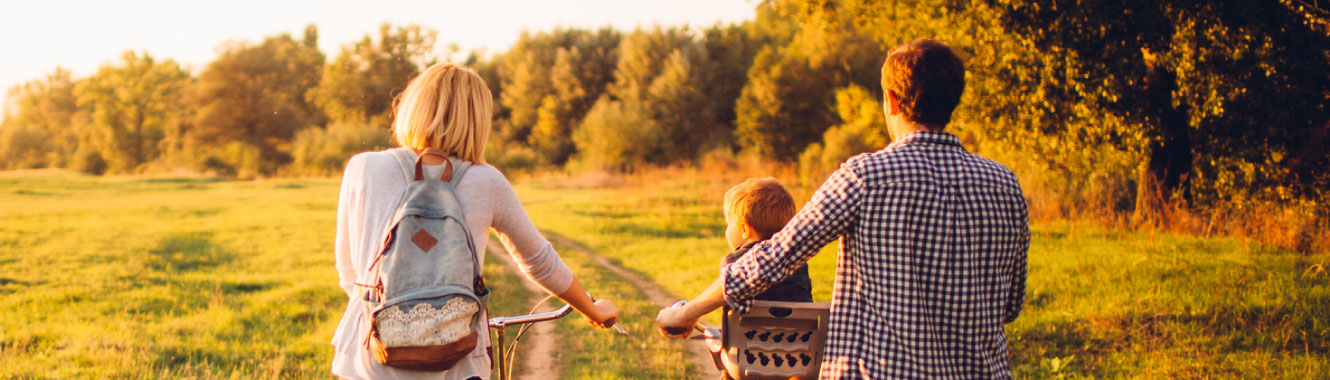 A young family pushing bikes in a field.